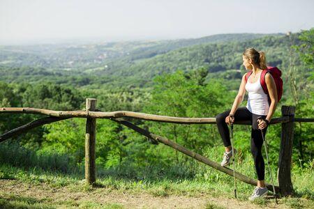 triplet: Beautiful hiker woman enjoying the view of a stunning green landscape below her