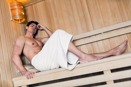 towel wrapped: Handsome man relaxing in a sauna with towel wrapped around his waist