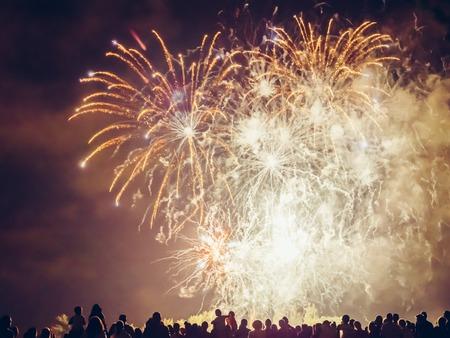 fuegos artificiales: Multitud wathcing fuegos artificiales y la celebración
