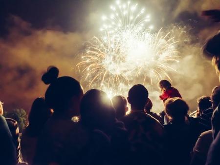 Multitud wathcing fuegos artificiales y la celebración