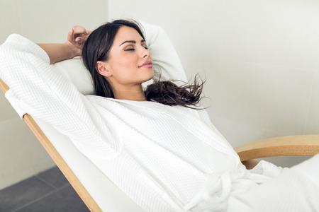 Retrato de uma mulher saudável nova bonita que relaxa em um robe
