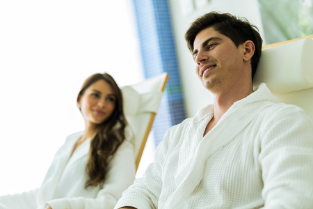 bath robe: A handsome man and a woman relaxing in a chair at a spa
