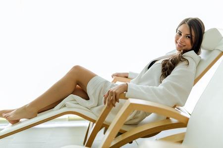 セクシーで美しい女性の衣を着て、笑みを浮かべて椅子でリラックス