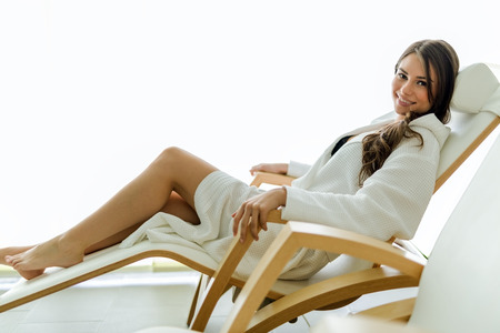 Sexy and beautiful woman relaxing in a chair dressed in a robe and smiling Stock Photo