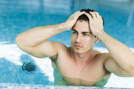 hombres sin camisa: Hombre que toca su cabello en la piscina levantando su mano Foto de archivo