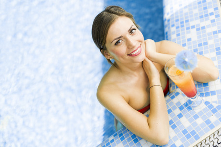 hot sexy girl: Beautiful woman in a pool with a cocktail next to her Stock Photo
