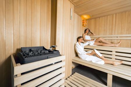 finland sauna: Sauna heater in a cozy sauna and girls relaxing in the background