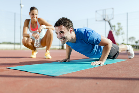 outdoor training: Young, beautiful, fit and healthy personal trainer counting push-ups and motivating