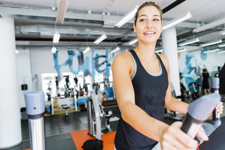 elliptic: Young fit woman using an elliptic trainer in a fitness center and smiling