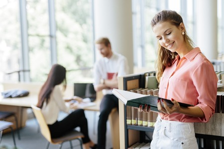 book shelves: Beautiful woman reading a book in a library and thinking Stock Photo