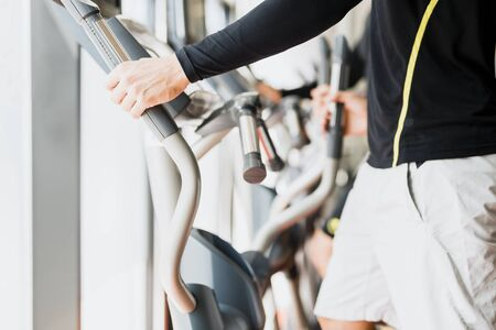 elliptic: Young healthy group of people working out on a elliptic trainer in a fitness center Stock Photo