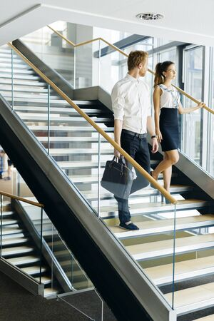 Businessman and businesswoman walking and taking stairs in a modern office building Stock Photo