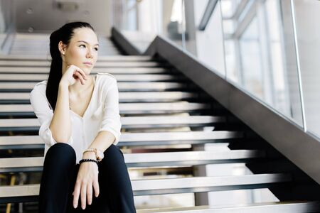 person walking: Businesswoman sitting on stairs and thinking. Fashion style photo
