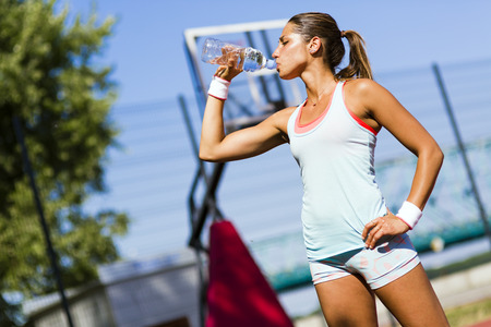 tomando agua: hermosa joven atleta de agua potable después de hacer ejercicio para revitalizar