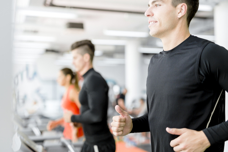 group fitness: Group of young people running on treadmills in a fitness center Stock Photo