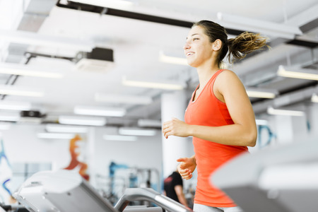 Beautiful young woman running on a treadmill in gym and smiling