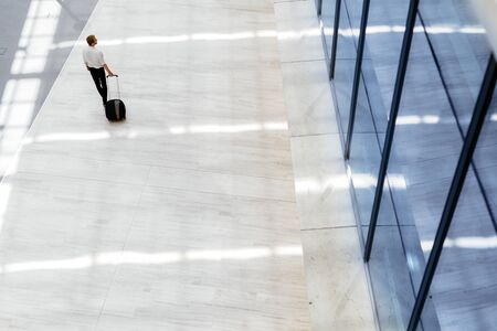 triplet: Handsome business holding a trolley and walking in a modern building seen from above