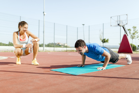 personal trainer: Young, beautiful, fit and healthy personal trainer counting push-ups and motivating