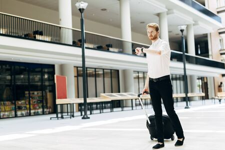 triplet: Handsome business holding a trolley and walking in a modern building