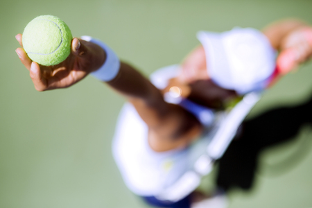 Jugador de tenis de sexo femenino hermoso que sirve al aire libre y un primer plano del saque desde arriba Foto de archivo - 44323756