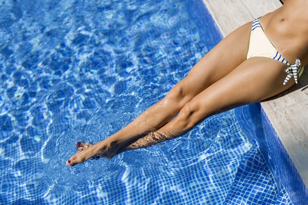 woman resting: Closeup of beautiful female legs in water of a pool Stock Photo