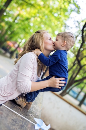 women kissing women: Parent touching noses with her son and smiling happily