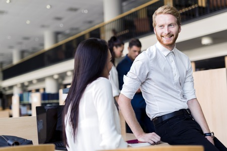 conversing: A group of academics studying in the library and conversing in a positive mood