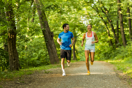 personas trotando: Young people jogging and exercising in nature