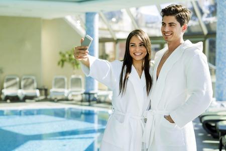 Pareja en el amor de pie junto a una piscina con una túnica y relajante