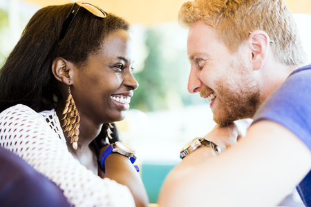 hombres negros: Romantic couple smiling while looking into each others eyes with love
