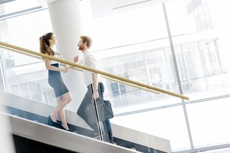 flirting: Business colleagues talking on stairs and flirting