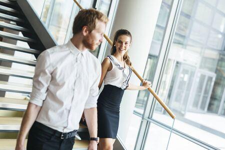bewegung menschen: Businessman and businesswoman walking and taking stairs in a modern office building Lizenzfreie Bilder