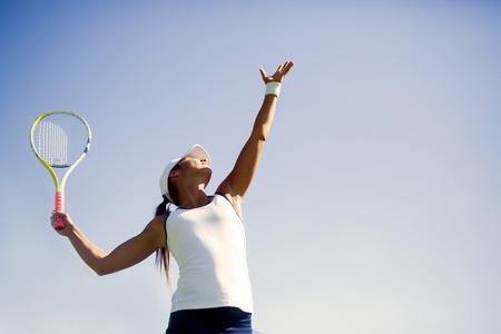 Schöne weibliche Tennisspielerin Servieren im Freien Standard-Bild