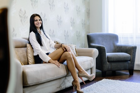 hot legs: Elegant and sexy woman sitting on a sofa in a luxurious room and smiling