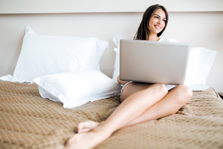 Beautiful young woman with sexy long legs in shirt using a notebook in bed Stock Photo