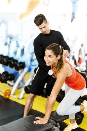 personal trainer: Young male trainer giving instructions to a woman in a gym and being supportive