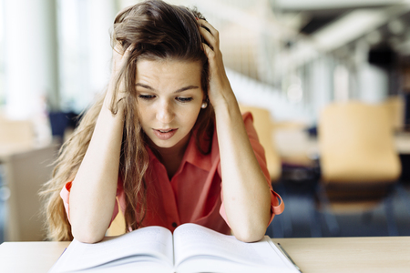 reading material: Female student studying and reading in a library but is having a hard time understanding the material Stock Photo