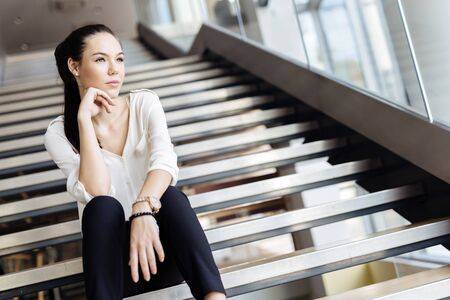 escalera: Empresaria que se sienta en las escaleras y el pensamiento. Estilo de la moda de fotos Foto de archivo