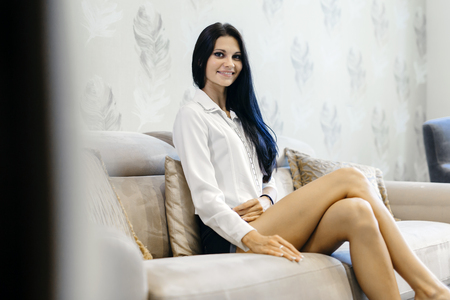 attractive couch: Elegant woman sitting on a sofa in a luxurious room and smiling