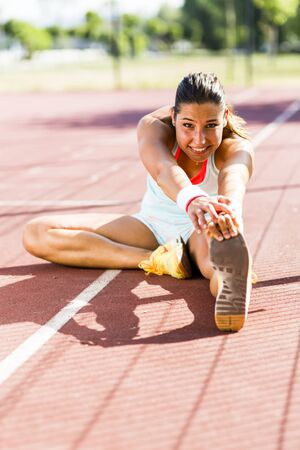 women sport: Beautiful young athletic woman stretching in summer before running Stock Photo