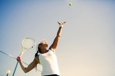 Mooie vrouwelijke tennisser serveren buiten