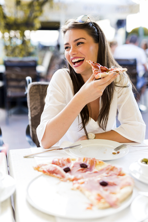 young girl: Beautiful young woman eating a slice of pizza in a restaurant  outdoors Stock Photo