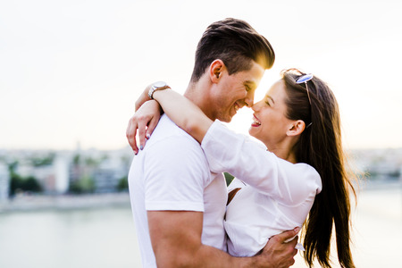 romântico: abraços casal romântico jovem e prestes a se beijar no belo pôr do sol Imagens