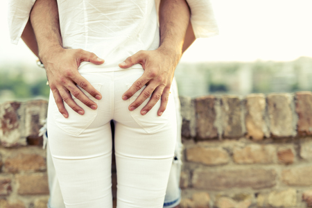 grabbing back: Sexual desire displayed by hands placed on butts Stock Photo