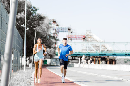 jogging track: A man and a woman jogging on a city track Stock Photo