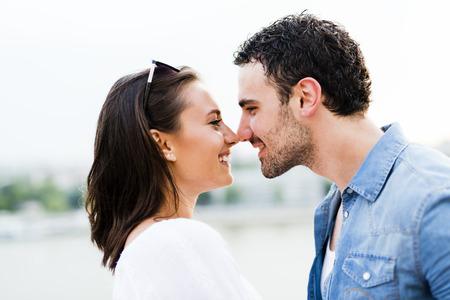 beso: Pareja joven hermosa frotando la nariz en señal de amor y a punto de besarse Foto de archivo