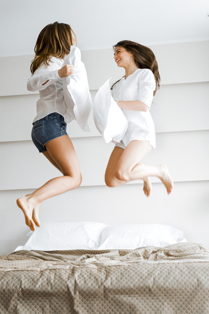 Two beautiful women jumping from joy on bed and fighting with pillows in a luxurious hotel room Stock Photo