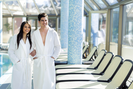 hotel with pool: Couple in love standing next to a  pool in a  robe and relaxing