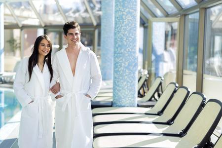 parejas: Pareja en el amor de pie junto a una piscina con una túnica y relajante Foto de archivo