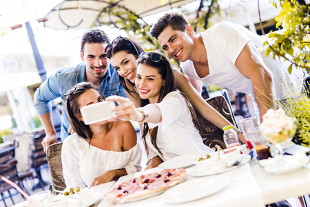 group photo: Group of young beautiful people sitting in a restaurant and taking a selfie while smiling Stock Photo